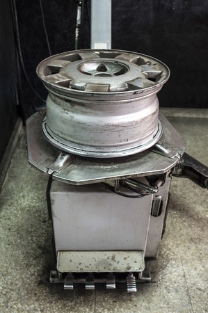 Rim with no tyre over mounting machine. Installing wheel process Stock Photo