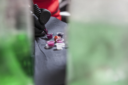 Tattoo artist refilling pen from small cups full of colorful inks. Picture taken between liquid bottles