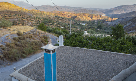 Blue chimney house with pebbles flat roof. Lecrin Valley, Alpujarras, Spain