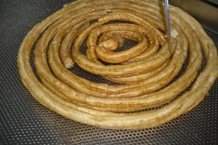 Churros preparation at Churros shop or churreria. Cutting the wheel