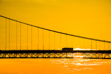 Truck crossing suspension bridge at sunset. Forth Road Bridge in North Queensferry, Scotland