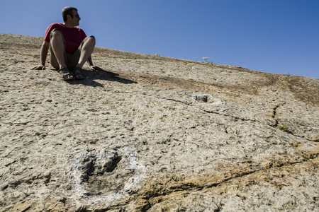 Espichel Cape, Portugal - June 19th, 2011: Tourist sitting close to several dinosaur fossil trackways exposed in some of Jurassic strata at Cape Espichel Rock cliff, Sesimbra, Portugal