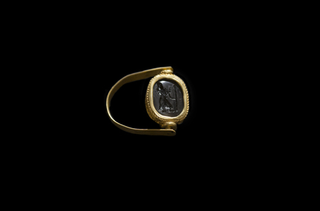 Aliseda, Spain - Octibre 29, 2017: Gold ring with glassy paste depiction belong to tartessos treasure of Aliseda. Replica currently kept at Interpretation Centre of Aliseda, Caceres, Spain Editorial