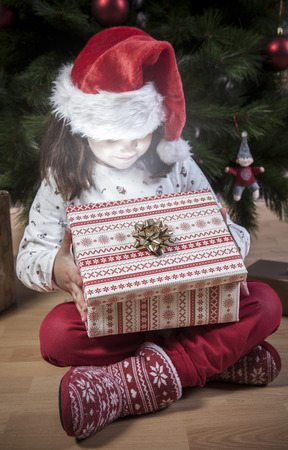 Little girl opening her present beside Christmas tree. She is illuminated by shine from box Stock Photo