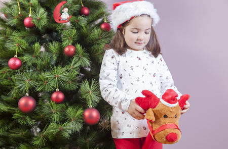 Little child girl playing with stick plush reindeer toy beside Christmas Tree at home