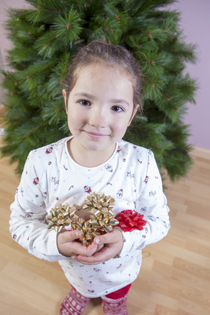 Merry Christmas and Happy New Year. Smiling little girl with a lot of ribbons for Christmas tree decoration. She is very, very happy