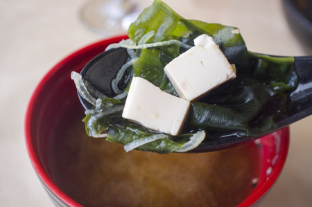 Japanese miso soup with tofu and seaweed. Clay spoonful closeup with two tofu pieces