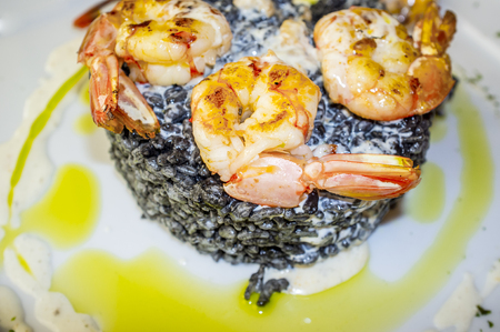 King prawns grilled with a side of black rice seasoned with olive oil and mayonaisse. Overhead closeup Stock Photo