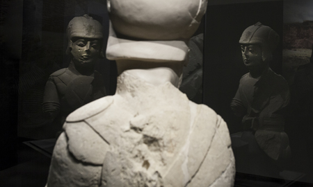 Jaen, Spain - December 29th, 2017: Warrior with double armour at Iberian Museum of Jaen. Back and front on glass reflections