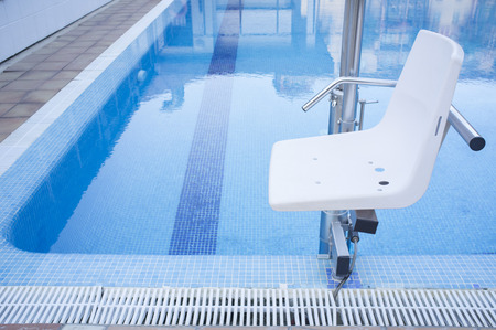 Swimming pool lift for disabled people access to the pool. Holidays resort background