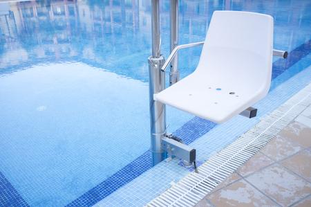 Zwembadlift voor gehandicapten toegang tot het zwembad. Vakantie resort achtergrond