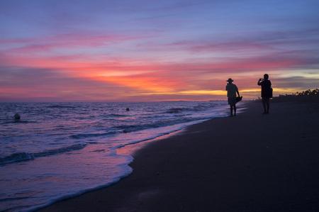 Elder tourist couple taking pictures at Islantilla beach during the magnificent sunrise. Huelva, Spain Stock Photo