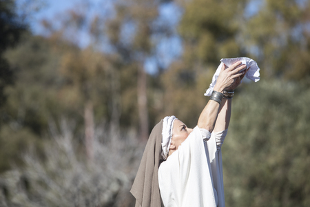 Alcuescar, Spain - December 17th, 2017: Reenactment of Iberian Goddess Ataecina ritual. Priestess rising arms with offering. Performed by Lusitania Romana Group