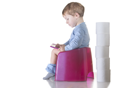Baby sitting on chamber pot reading a book. Potty training concept Stockfoto