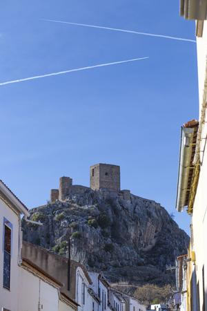 Outcrop rocky hill with Castle of Belmez, Cordoba, Spain. Jet contrails over blue sky