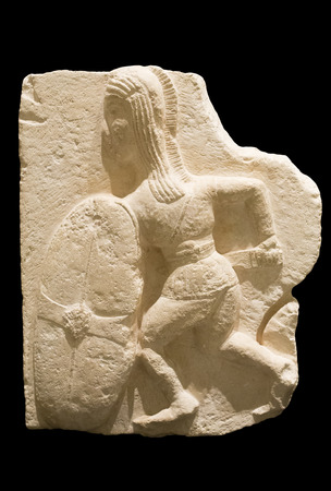 Madrid, Spain - November 10, 2017: Young Iberian warrior carrying a scutum or shield. Half relief belong to Osuna group at National Archaeological Museum, Madrid