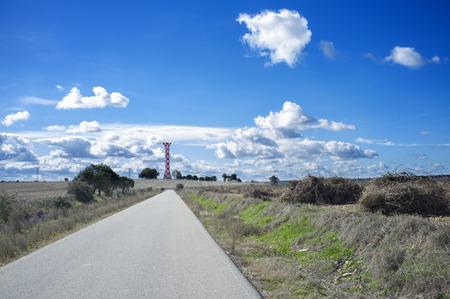 Road to Irrigation water tank. Torre in cemento realizzata per l'irrigazione del negozio di acqua, Vegas Bajas del Guadiana, Extremadurs, Spagna
