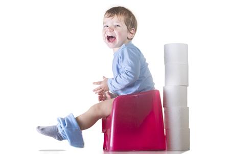 Happy baby boy sitting on chamber pot. Potty training concept Standard-Bild