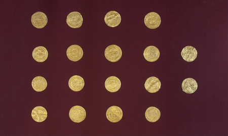 Jaen, Spain - December 29th, 2017: Golden Almoravid dinars with carved arabic scripts, Jaen Archeological Museum