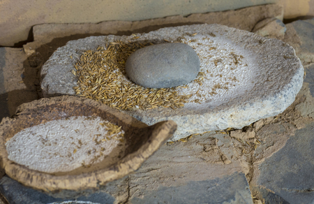 Jaen, Spain - December 29th, 2017: Neolithic era hand mill stone with barley and flour bowl made of cork. Selective focus. Jaen Museum 免版税图像 - 98436472