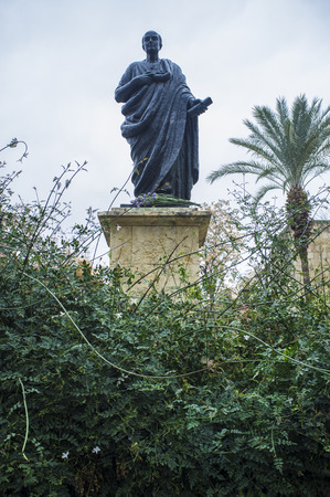Bronze Statue of Seneca the Younger between jasmine garden, Roman Stoic philosopher. Cordoba, Spain