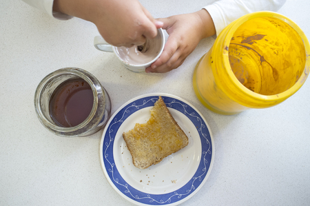 Little girl preparing her afternoon snack. Chocolate powder with milk, honey and toast Stock Photo