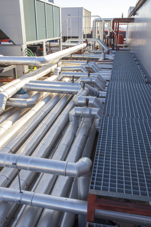 Industrial Heating Ventilation and Air Conditioning at building roof. Platform footbridge over pipes 스톡 콘텐츠