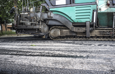 Work on the laying of asphalt in the city. Paving applicator machine or paver at work