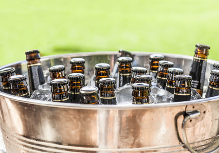 Beer bottles on ice bucket with green grass background. Closeup
