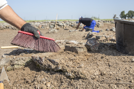 Specialized workers with brush on archaeological excavation. Visible clay pieces Stock Photo