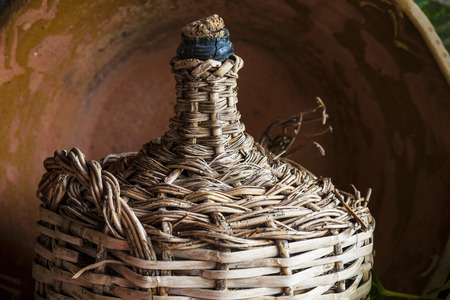 Old lined wicker carafe former used for home wine transport. Closeup