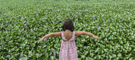 Child girl over invasive water hyacinth, taking over the whole course of Guadiana River, near Badajoz, Spain