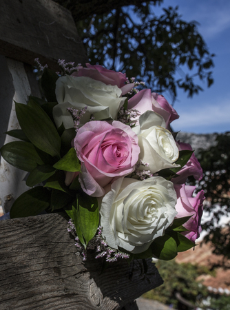 Wedding bouquet with pink and white roses on weathered wooden ladder. Spanish country style background Stok Fotoğraf