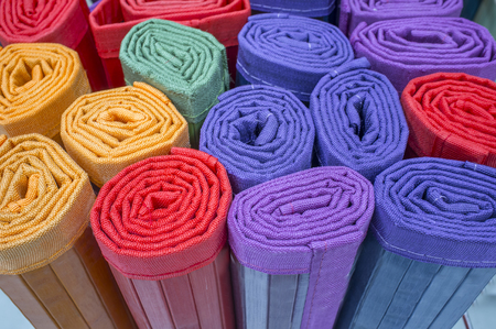 Loads of many rolled colorful light ratan carpets. Closeup