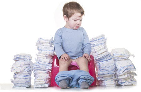 Niño triste sentado en el orinal porque debe dejar de usar pañales. Concepto de entrenamiento para ir al baño