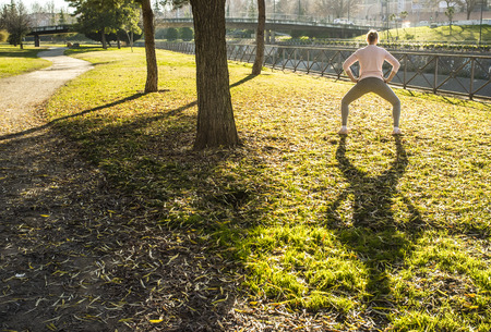 Woman doing stretching exercises at urban park in autumn season. Get in Shape in Your 30s concept Stock fotó