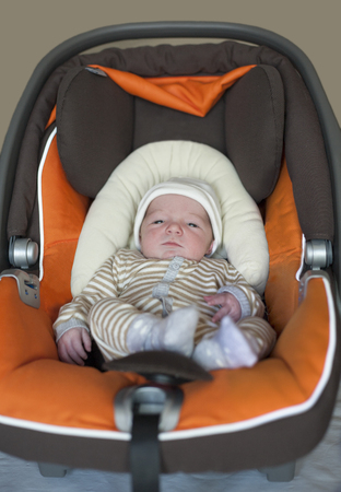 Baby newborn at i-size baby car seat type. Few days-old baby at home Standard-Bild
