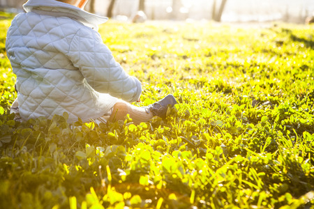 9 month baby under sun rays  on grass park. Benefits of Sunlight for babies concept