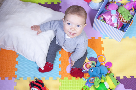 7 months baby boy sitting over puzzle play mat. Learning to sit up concept