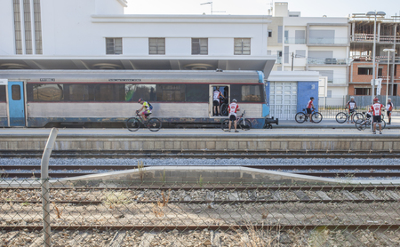 VR Sto Antonio, Portugal - Sept 30th, 2017: Mountain bikers getting down from train at railway station, Algarve, Portugal Editorial