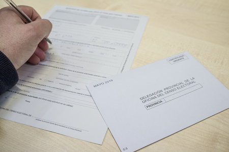 Mature man filling request for absentee vote or postal vote. 2019 Spanish general election 免版税图像