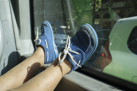 Bored little boy going by bus. He is wearing a blue deck shoes that place on glass Stock Photo