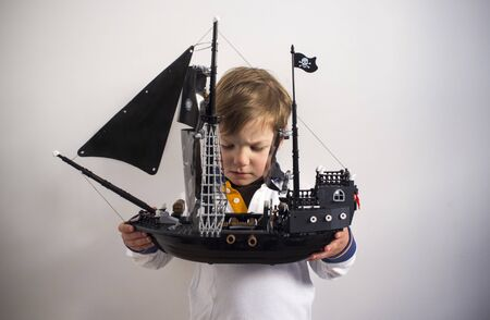 3 years boy observing his pirate toy ship. Traditional toy for promote imagination Stock Photo