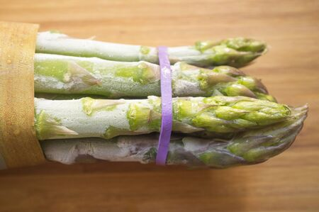 Bunch of frozen wild asparagus tied with rubber tape from ecological agricuture over wooden background. Overhead shot