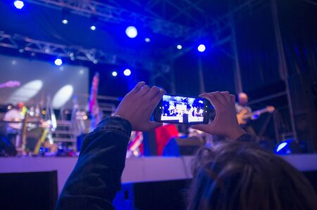 A woman with his smartphone takes a picture in a concert. Selective focus