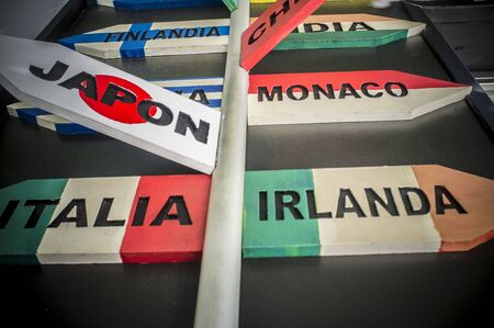 Pole guidepost with multiple destination countries of the world on arrows sticks in Spanish. Low angle view Imagens