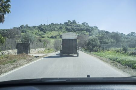 Slow horses transport on local road. The road is fully occupied by trailer Stock Photo