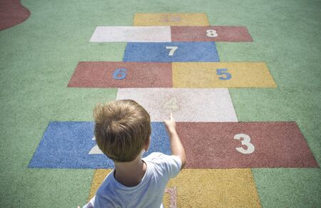 Boy learning numbers at rubber hopscotch. Numbers on the pavement. Early Education at Mathematics and Numeracy concept for children