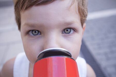 Little drinking from soft drink can. Children with unhealthy habit about sugary soft drinks Banco de Imagens