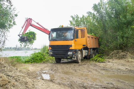 Heavy machinery removing water hyacinth from riverside. Highly problematic invasive alien specie (IAS) at Guadiana River, Badajoz, Spain Stock Photo